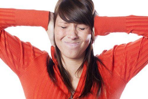 Fille qui a mal aux oreilles car elle a des acouphènes.