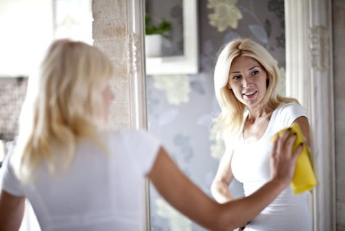 Femme qui est en train de nettoyer un miroir.