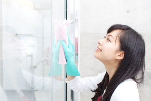 Femme en train de nettoyer la paroi de douche.